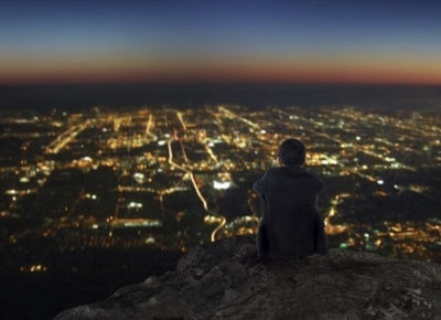 A man standing on a hill over a town at dusk. He's pondering his kingdom impact.